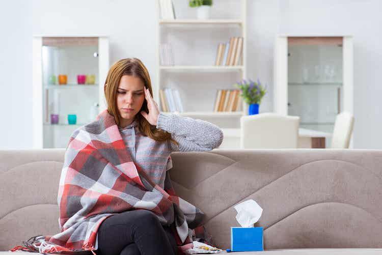 Ragazza sul divano combatte i sintomi di raffreddore e catarro.