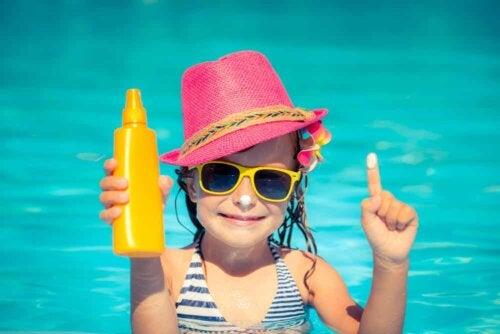 Bambina con crema solare e occhiali da sole.