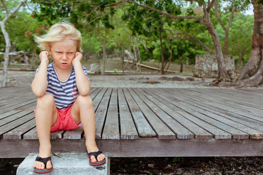 Bambino capriccioso seduto a terra.