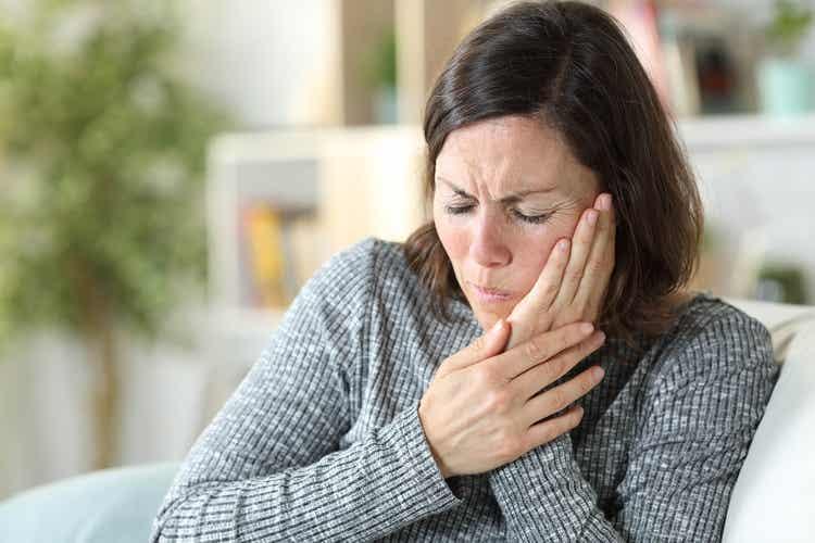 Donna con mal di denti causato dai denti impattati.