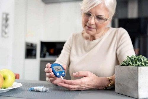 Donna anziana misura la glicemia.