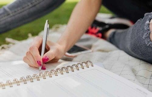 Donna che scrive su un quaderno ad anelli.