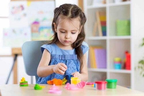 Bambina gioca con la plastilina.