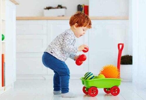 Bambino che raccoglie giocattoli.