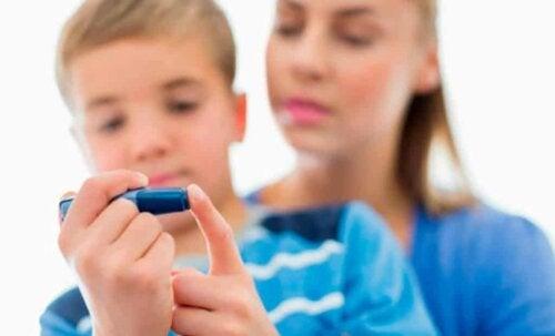 Bambino che si misura il livello di glicemia.