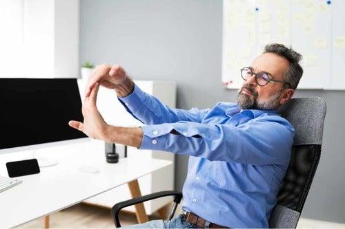 Uomo che fa stretching davanti il computer per affrontare al meglio la vecchiaia.
