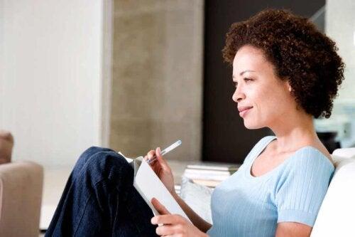 Donna che scrive il proprio diario della gratitudine.