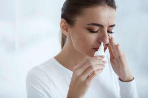 Donna che applica uno spray nasale.